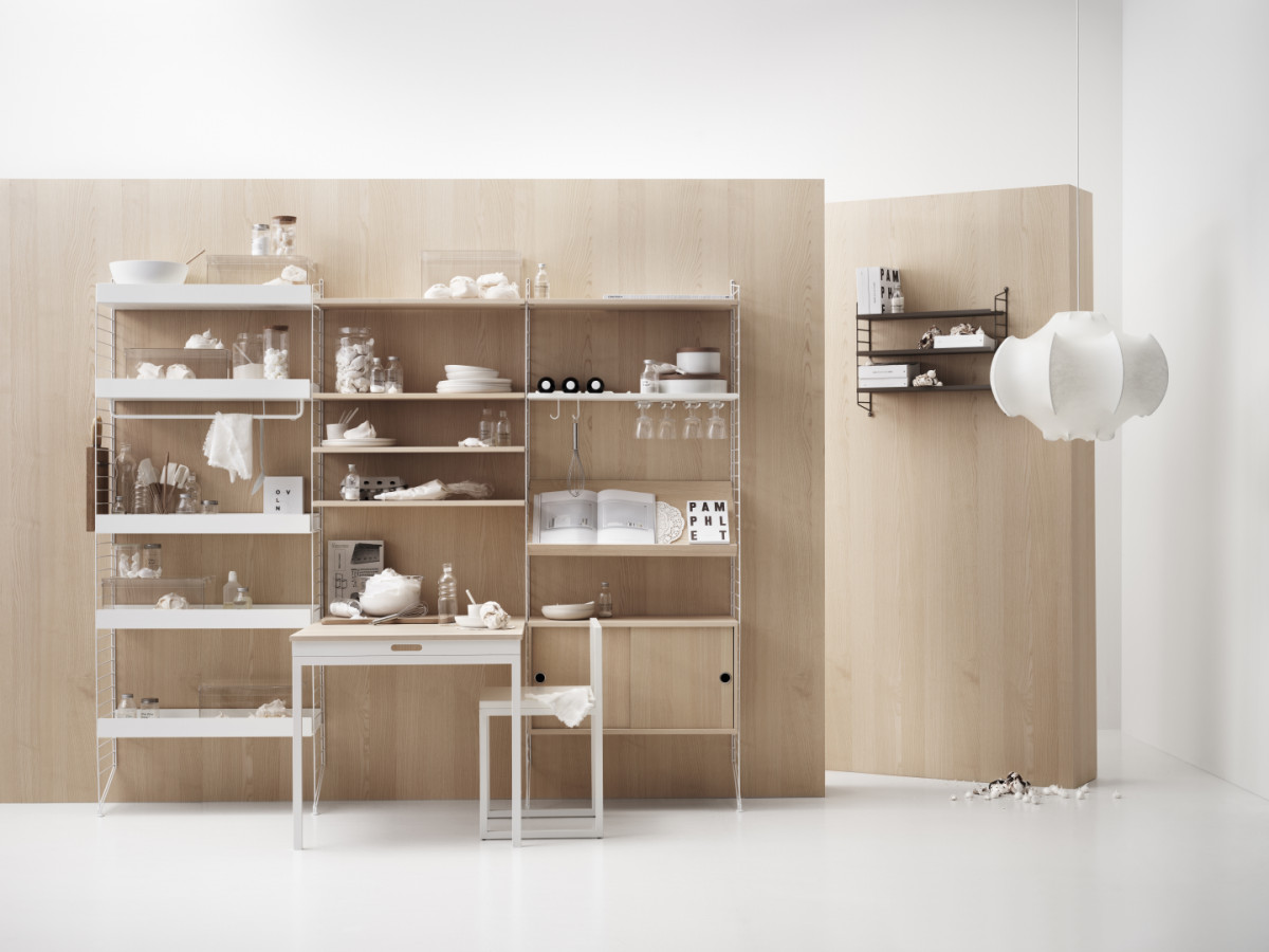 Floor mounted kitchen solution from String. Floor panels in white. Metal shelves high and low, rods, hanger racks, and hooks in white. Shelves, folding table and cabinets with sliding doors in ash.
