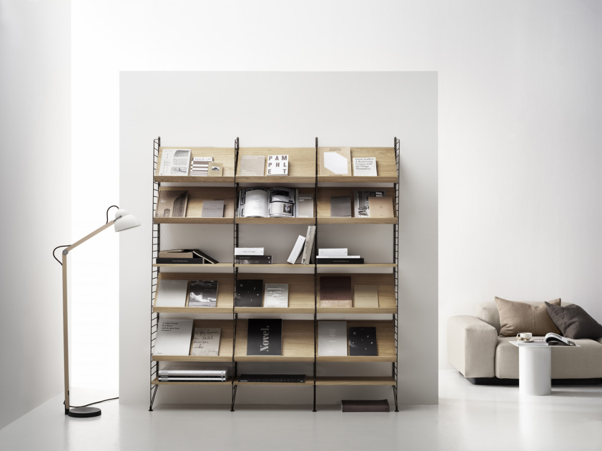 Floor mounted living room solution from String.Floor panels in brown. Magazine shelves and shelves in ash.
