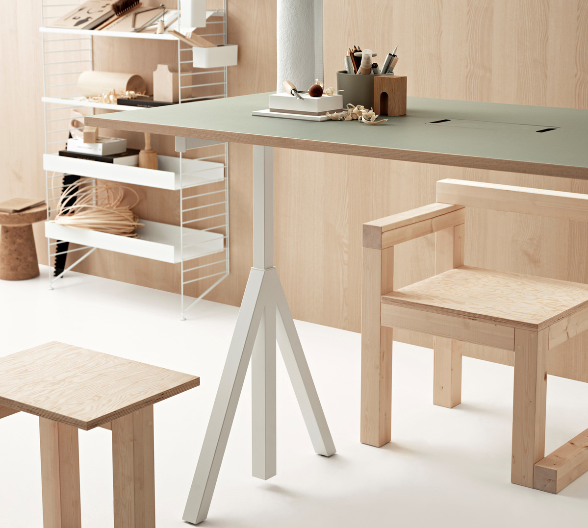 Floor mounted workspace solution from String. Floor panels, metal shelves high and low, metal shoe shelf and organizers in white. Sit-stand table from Works™ ..by String Furniture. With a white base and a modern coloured tabletop in light grey linoleum. A modern design on a classic height-adjustable office table.