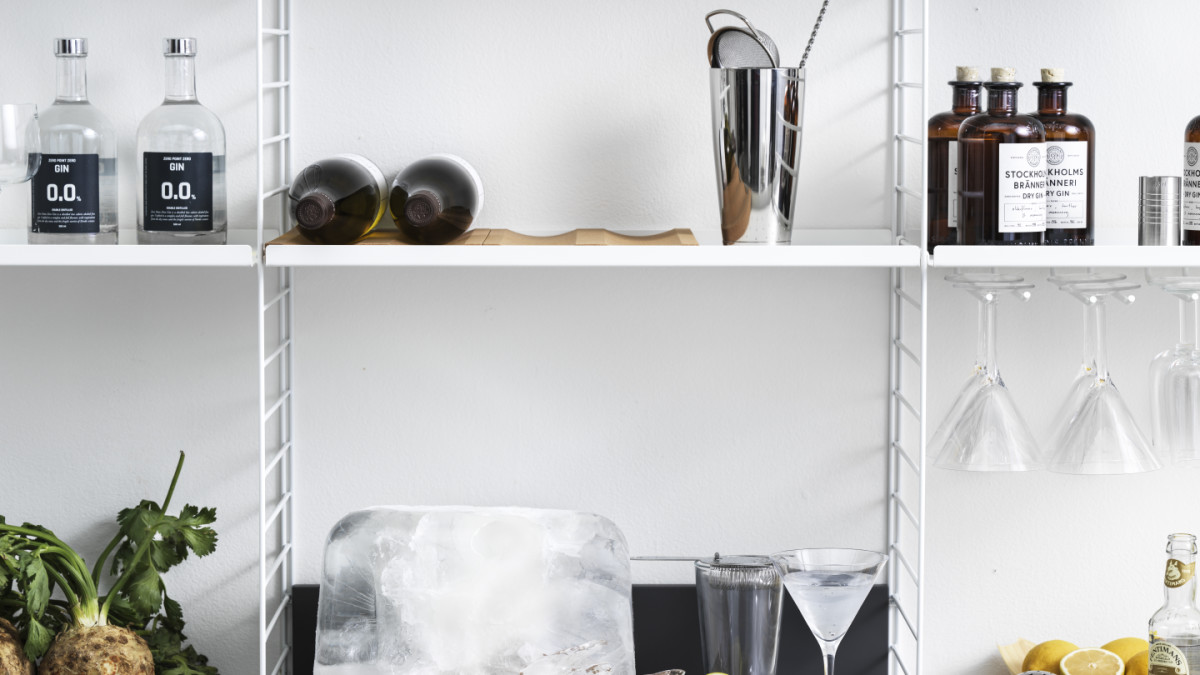 String shelf with floor panels from String System. Panels, metal shelves with low edge, metal shelves with high edge, and hanger racks white. Media shelf in anthracite grey, bottle tray in cork, divider in cork, and underlay in cork. This shelving combination is perfect in a kitchen or living room where the media shelf can be used as a drink table.