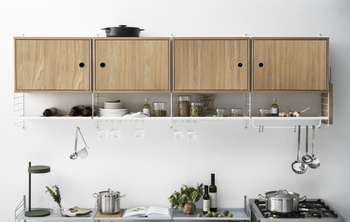 String shelf with white wall panels and metal shelves with low edge in white along with cabinets with swing door in oak. Accessories such as rods, hanger racks, plate racks in white, organizers in beige, s-hooks in stainless steel along with a knife holder in massive oak.