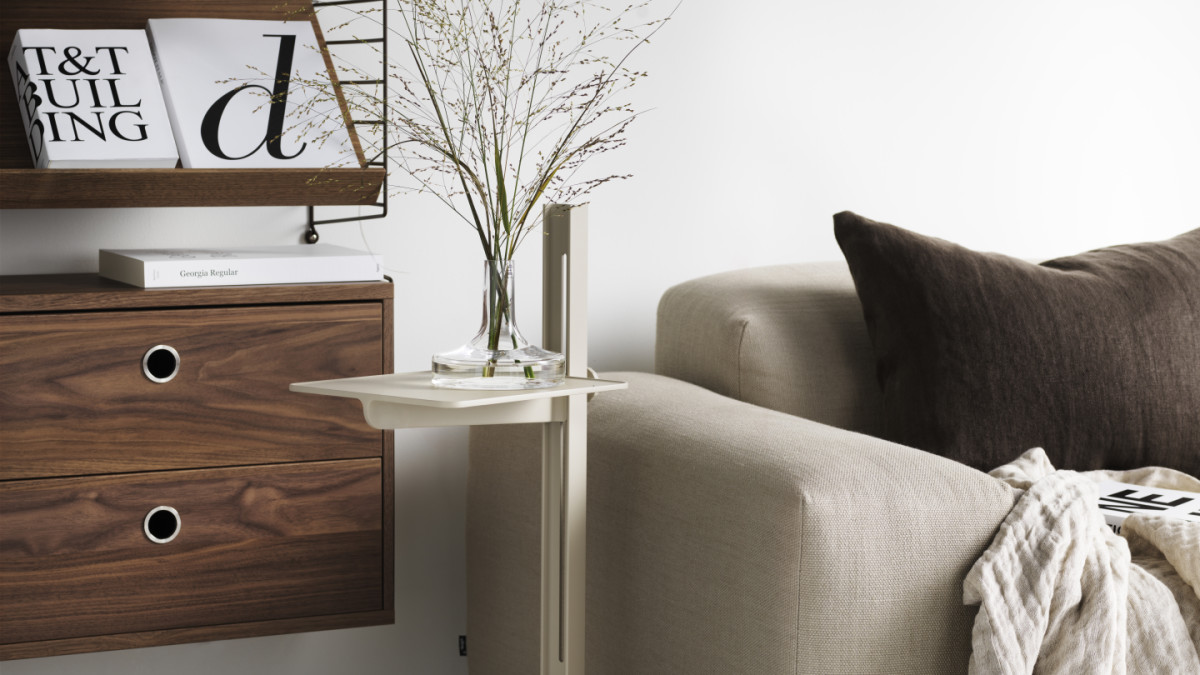 Shelving combination perfect for your living room . Wall-hung shelving combination with brown panels, shelves, magazine shelves and drawers in walnut. Complement you string shelf with a Museum sidetable in beige.
