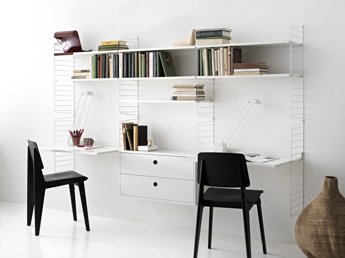 Wall-hung string shelf in white. Shelves, work desks and drawers creates two separate work stations.
