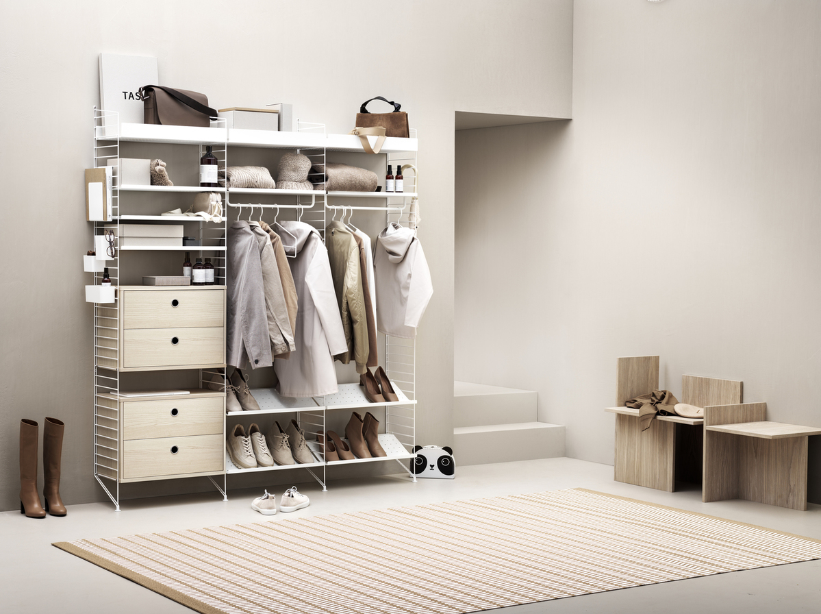 Hallway combination from String shelving system. Floor panels, metal shelves low, metal shelves high and shoe shelves in white. Chest of drawers in ash. Magazine holder, coat hangers, rod, hangers and hooks in white.