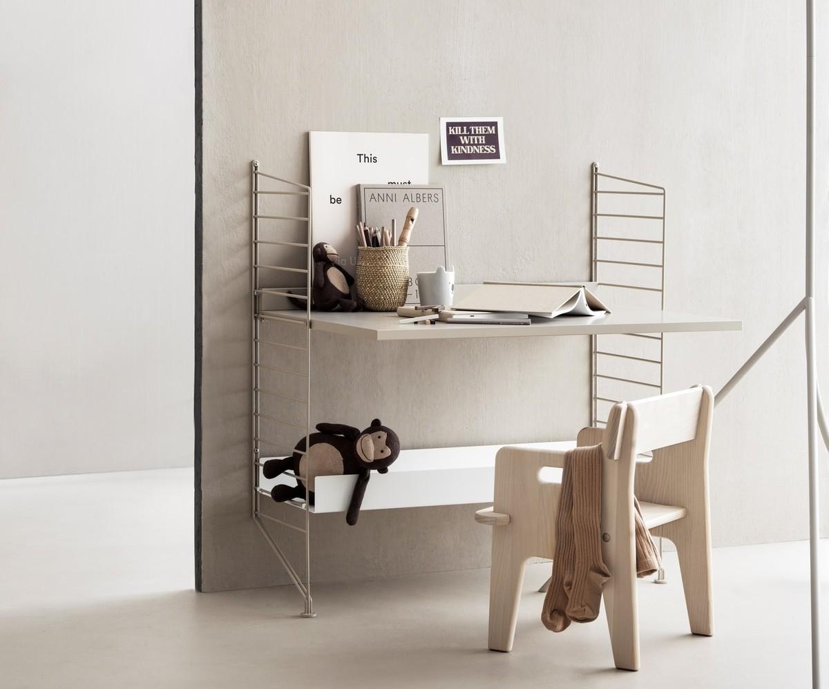 Floor mounted kids room solution from String. Floor panels and work desk in beige. Metal shelf high in white.