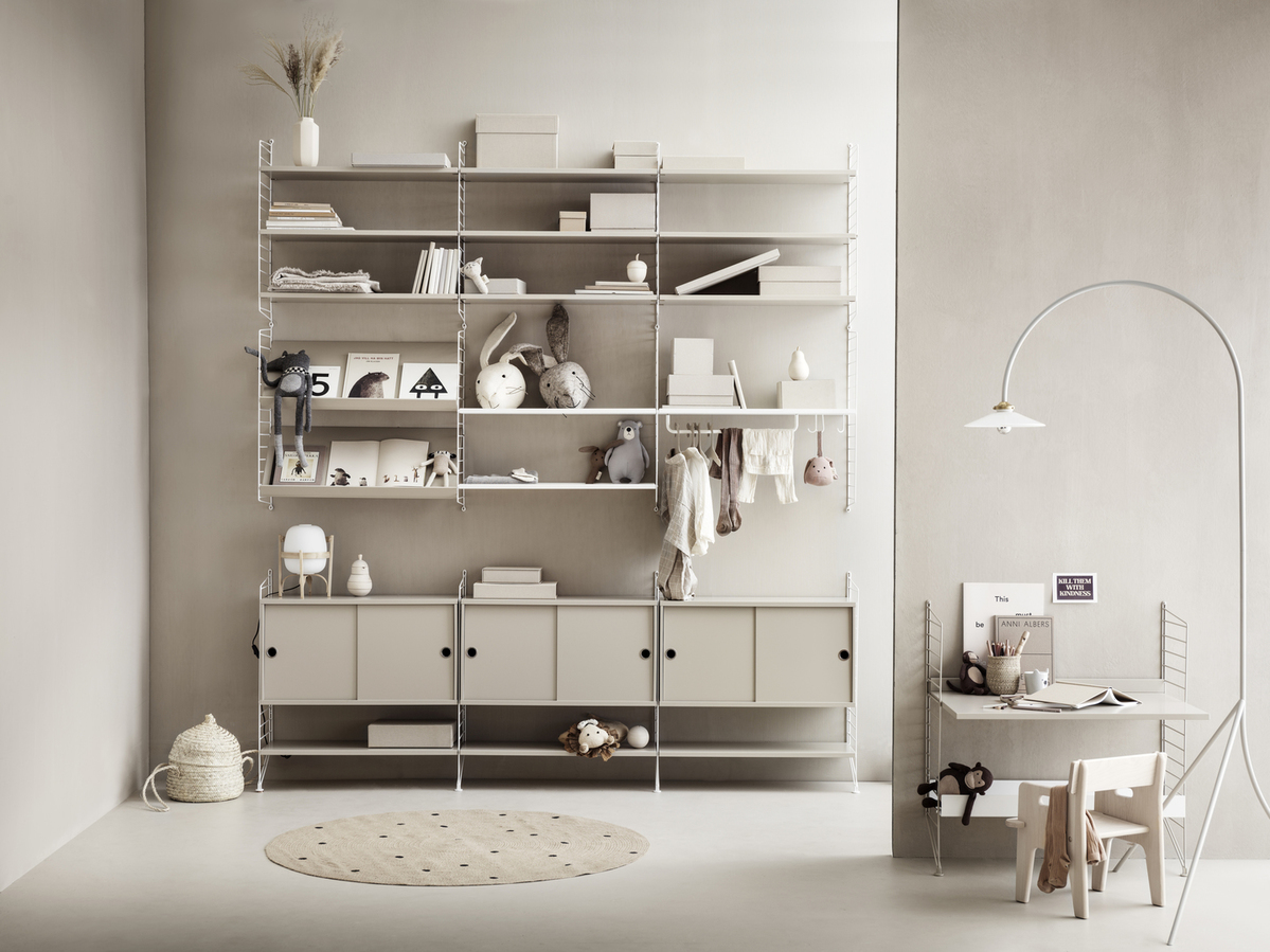 Floor mounted kidsroom solution from String. Floor panels and wall panels in white. Shelves, cabinets with sliding doors, magazine shelves solid and work desk in beige. Metal shelves low and metal shelf high in white. Rod and hooks in white.