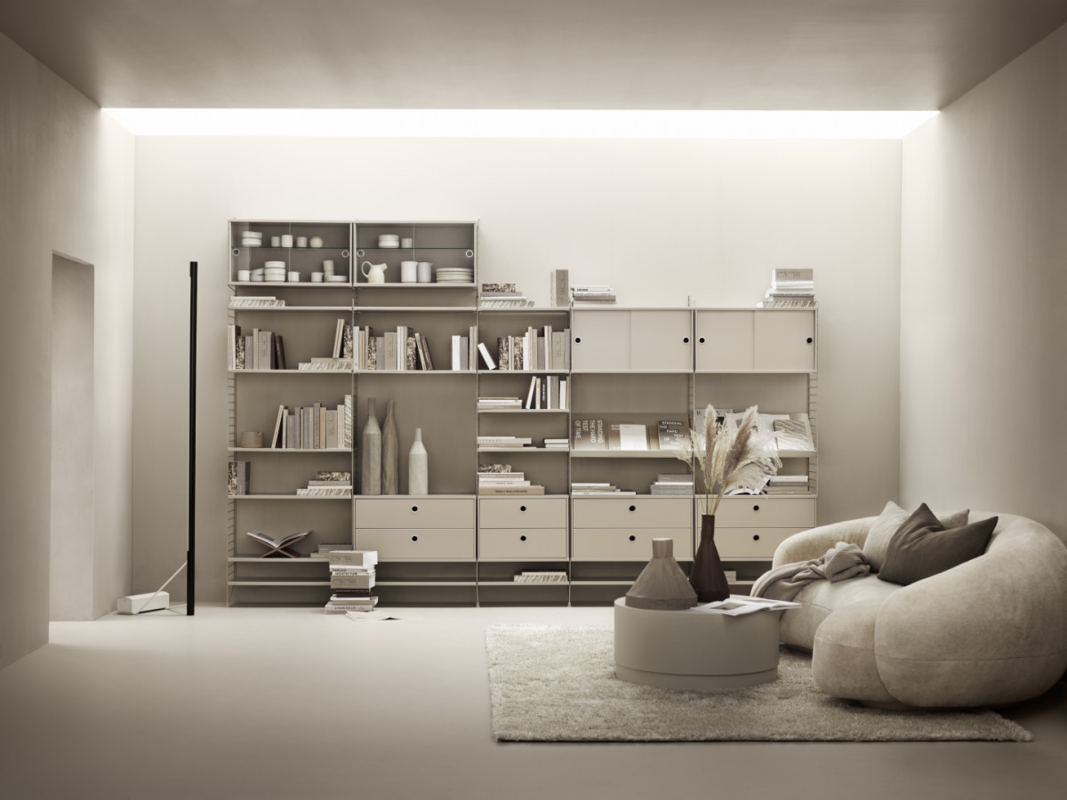Floor mounted living room solution from String. Floor panels, wall panels, shelves, chest of drawers, cabinets with sliding doors, cabinets with sliding glass doors and magazine shelves solid in beige.