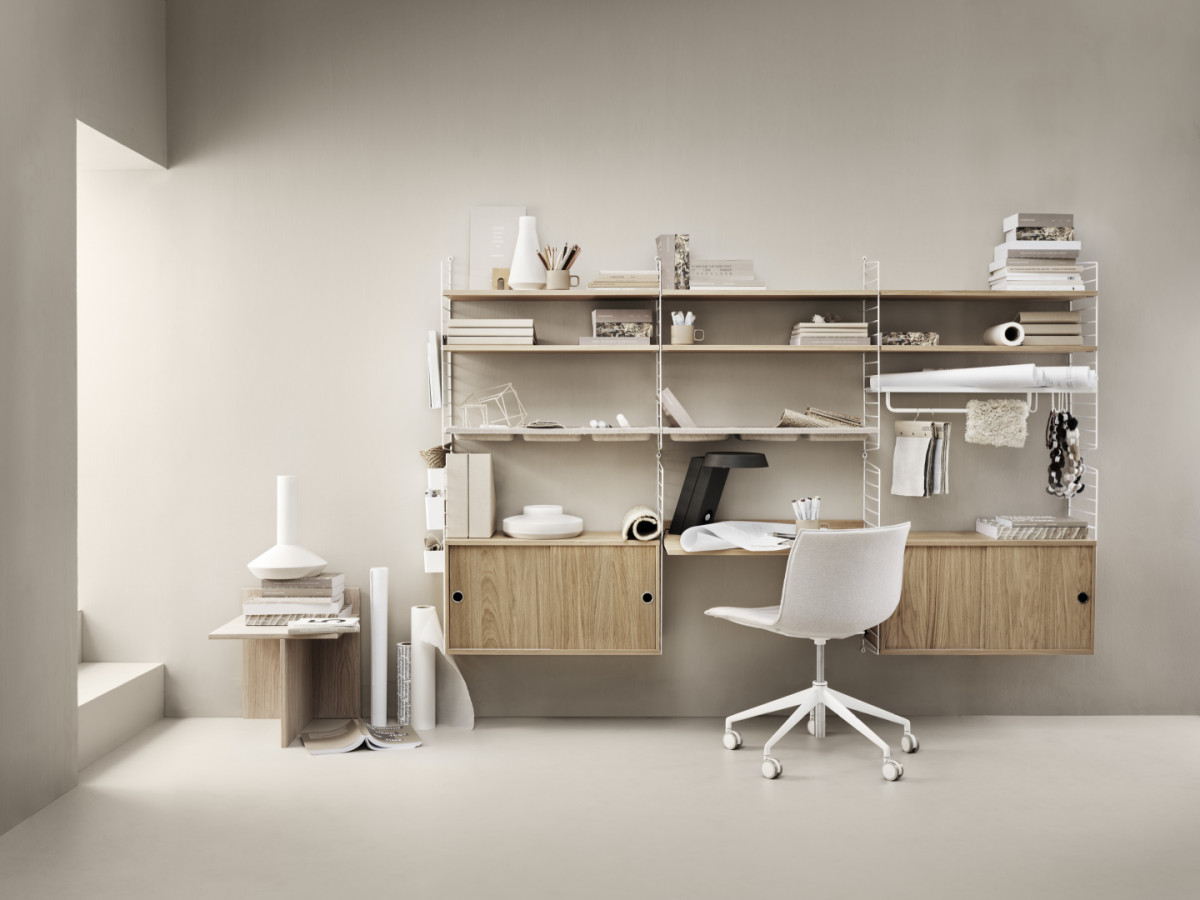 String shelving system for your workplace. Wall panels in white, shelves in oak, bowl shelves in white, cabinets with sliding doors in oak, work desk in oak, organizers in white, magazine shelf in white, rod in white and j hooks in white