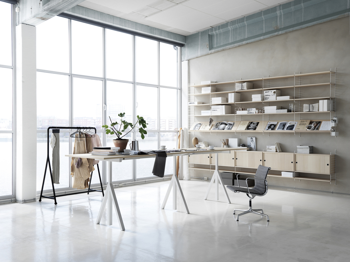 Wall mounted workspace solution from String. Height-adjustable conference table in ash. Wall panels in white. shelves and cabinets with sliding doors in ash.