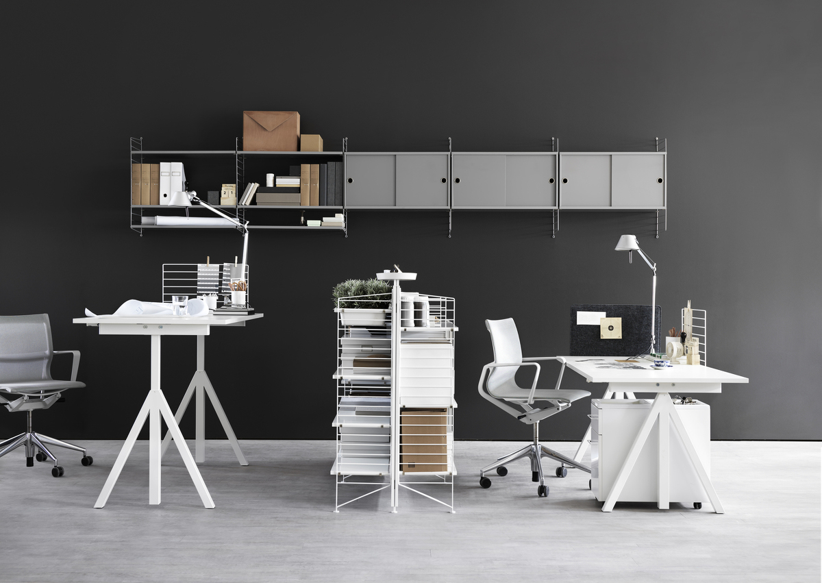 Wall mounted workspace solution from String. Height-adjustable work desk in white. Mobile storage in white. Wire screen in white. Fabric sleeve in grey felt. Freestanding shelf. Wall panels in grey. Shelves and cabinets with sliding doors in grey.
